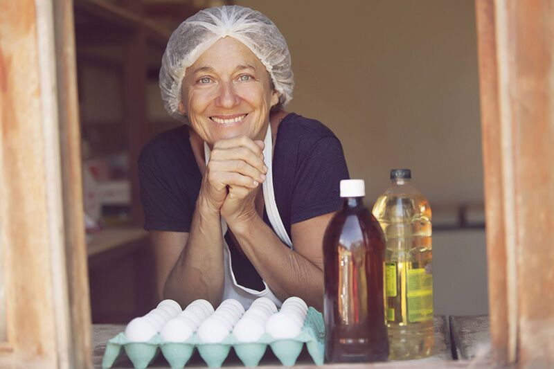 smiling baker at window of her small business, Formula One Retail Ordinances